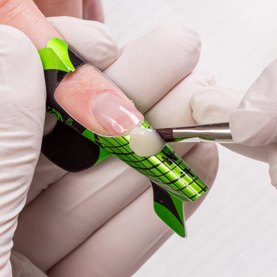 """Plaats het penseel met de schone kant op het sjabloon en """"rol"""" de Natural White van het penseel af. Breng de gel naar de natuurlijke nagel en corrigeer de vorm van de nagel. De Base gel en de Natural White vloeien in elkaar over waardoor er een natuurlijke overgang ontstaat. Hierdoor kan de nagel uitgroeien zonder zichtbare uitgroei. Hard dit vervolgens 2 minuten uit in de UV lamp."""
